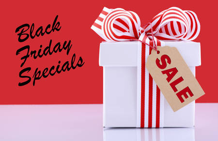 long weekend: Black Friday red and white sales promotion gift box on white reflective table against a red background with sample text.
