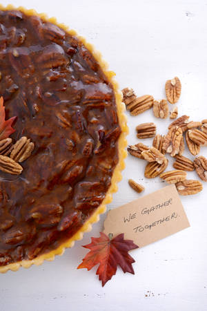 pecan pie: Traditional Thanksgiving Pecan Pie on rustic white wood table with We Gather Together place card.