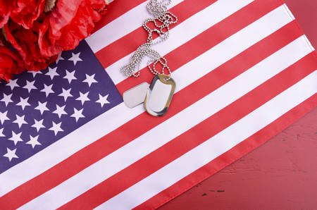 remembrance day poppy: Veterans Day USA flag with dog tags and red flanders poppies on rustic red wood background, overhead with copy space. Stock Photo