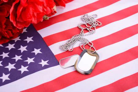Bandera Día de los Veteranos EE.UU. con placas de identificación y Flandes rojas amapolas en fondo rústico de madera roja Foto de archivo - 47937961