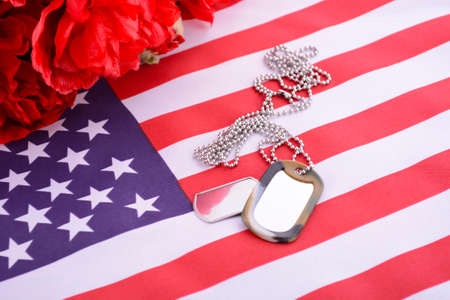 Veterans Day USA flag with dog tags and red flanders poppies on rustic red wood background Stock Photo
