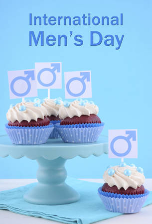 cake stand: International Mens Day Cupcakes on cake stand with Male Symbols on pale blue and white wood background, and sample text. Stock Photo