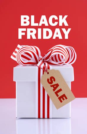 christmas savings: Black Friday red and white sales promotion gift box on white reflective table against a red background with sample text.