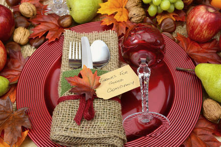 Rustic Thanksgiving with burlap wrapped cutlery, red crystal wine glass on large charger plate, and Fall harvest fruit and nuts.