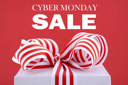 Cyber Monday red and white sales promotion gift box closeup against a red background with sample text.