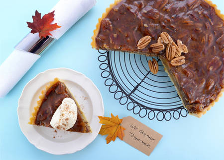 pecan pie: Happy Thanksgiving traditional pecan pie with individual slice on plate on pale blue wood table. Foto de archivo