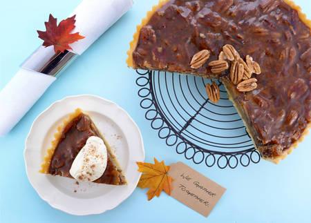 pecan pie: pastel tradicional de Acción de Gracias feliz pecan con la rebanada del individuo en el plato en la mesa de madera de color azul pálido.