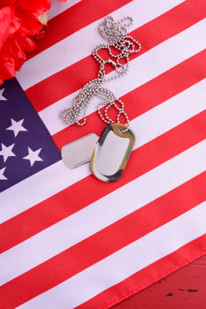 remembrance day poppy: Veterans Day USA flag with dog tags and red flanders poppies on rustic red wood background, overhead. Stock Photo