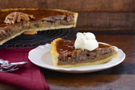 napkin ring: Traditional Thanksgiving individual serving of pecan pie on dark wood rustic wood table and background.