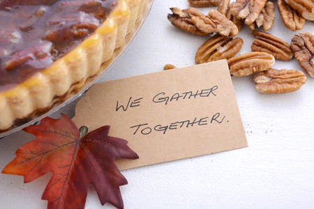 pecan pie: Traditional Thanksgiving Pecan Pie on rustic white wood table with We Gather Together place card, closeup.