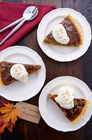 pecan pie: Traditional Thanksgiving Pecan Pie individual slices on plates overhead with We Gather Together place card on vintage dark wood table setting.