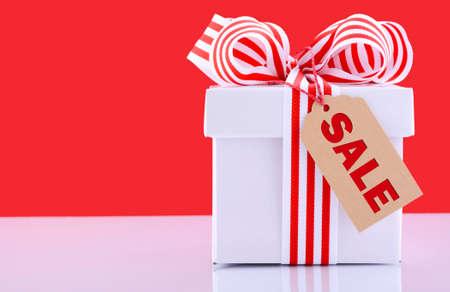 rode en witte sales promotion gift box op witte reflecterende tafel tegen een rode achtergrond.