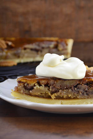pecan pie: Traditional Thanksgiving individual serving of pecan pie on dark wood rustic wood table and background, with copy space. .