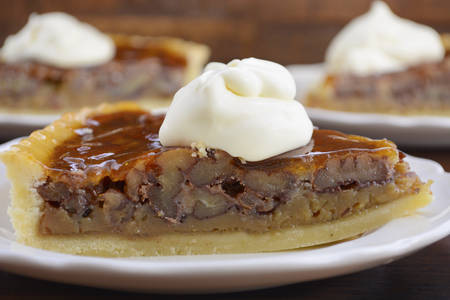 pecan pie: Traditional Thanksgiving individual serving of pecan pie on dark wood rustic wood table and background, closeup.