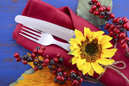 background settings: Happy Thanksgiving dark blue wood background with decorated borders of sunflowers and place settings, with closeup on details.