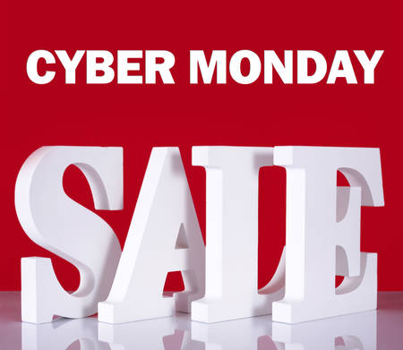 Photograph of Large white Sale letters made out of wood on reflective glass table with red background with Cyber Monday text.
