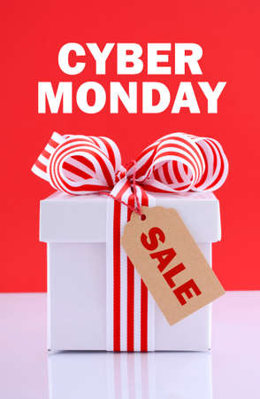 Cyber Monday red and white sales promotion gift box on white reflective table against a red background with sample text. Stock Photo