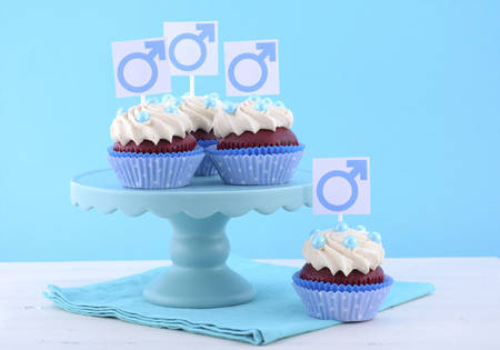 cake stand: International Mens Day Cupcakes on cake stand with Male Symbols on pale blue and white wood background.