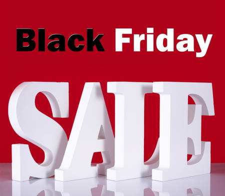 long weekend: Photograph of Large white Sale letters made out of wood on reflective glass table with red background with Black Friday text.