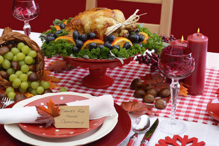 horn of plenty: Red and white theme Thanksgiving table with individual place setting, food and cornucopia. Stock Photo