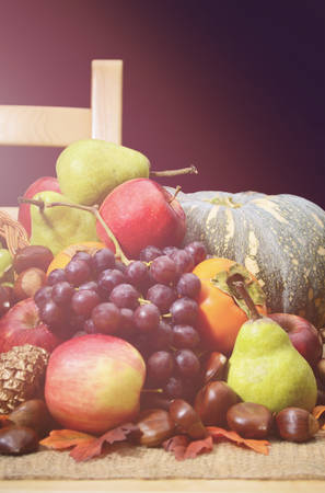 harvest cone cornucopia: Happy Thanksgiving rustic table and chair with Fall harvest fruit, nuts, pumpkin and cornucopia, with added retro vintage style filters and lens flare light stream. Stock Photo