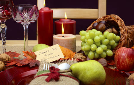 happy feast: Country style, rustic Thanksgiving table place setting closeup with chair, cornucopia, wine glasses, fruit, nuts and burning candles.