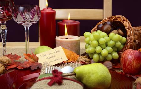 cuerno de la abundancia: estilo rural, r�stico de Acci�n de Gracias lugar de la tabla ajuste de cerca con la silla, cornucopia, copas de vino, frutas, frutos secos y velas encendidas.