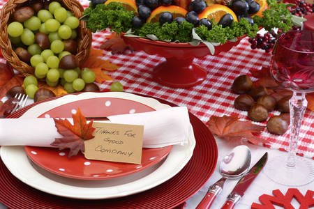 company party: Red and white theme Thanksgiving table with individual place setting, food and cornucopia, closeup on Thanks for Good Company place card. Stock Photo