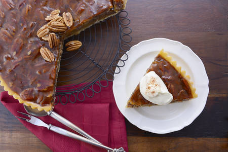 pecan pie: Traditional Thanksgiving individual serving of pecan pie on dark wood rustic wood table and background.