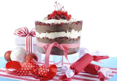 cioccolato natale: Foresta Nera sciocchezza dessert con strati di torta al cioccolato, cioccolato crema pasticcera, amarene e panna montata in cornice festosa, su sfondo bianco.