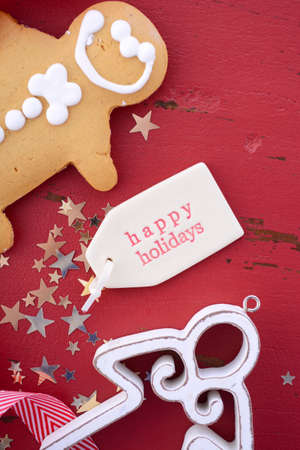 above 25: Christmas Happy background with white wood ornaments and gingerbread men cookies on red wood table, closeup on Happy Holidays gift tag.