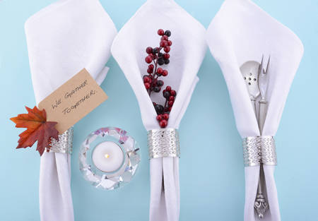 formal place setting: Happy Thanksgiving white linen napkins in a row with We Gather Together place card message on pale blue table with candle. Stock Photo