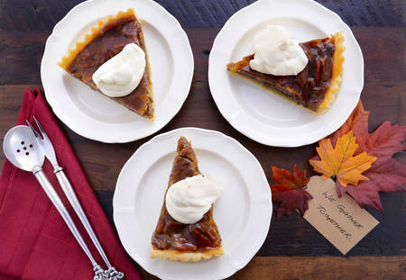 gather: Individual slices of pecan pie with whipped cream on dark wood vintage table with We Gather Together for Thanksgiving dessert.