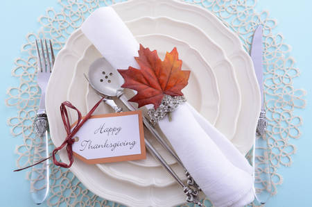 place setting: Happy Thanksgiving formal table place setting with fine china and vintage napkin ring on pale blue wood table.
