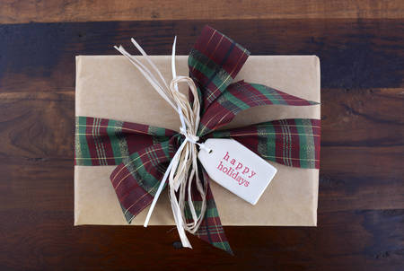 above 25: Rustic Christmas holiday gift in natural kraft paper gift box with Happy Holidays gift tag and traditional tartan ribbon on country style wood background.