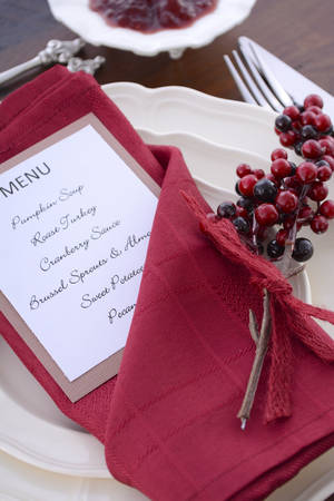 thanksgiving menu: Happy Thanksgiving table setting with Pumpkin Soup, Roast Turkey, and Pecan Pie listed on the Menu, with cranberry sauce in bowl on vintage wood table.