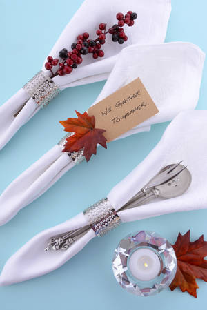 gather: Happy Thanksgiving white linen napkins in a row with We Gather Together place card message on pale blue table with candle. Stock Photo