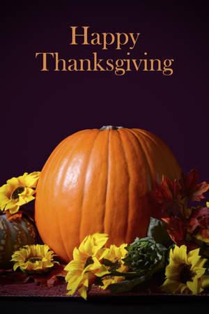 centerpiece: Thanksgiving pumpkin centerpiece on vintage tapestry table runner on dark background, spotlighted against dark background.