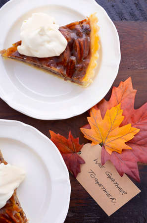 pecan pie: Individual slices of pecan pie with whipped cream on dark wood vintage table with We Gather Together for Thanksgiving dessert.
