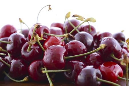 glycemic: Fresh black cherries fruit closeup against a white background.