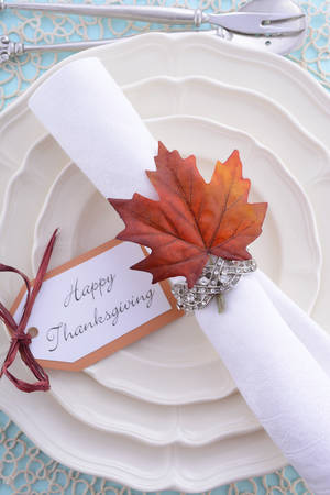 formal place setting: Happy Thanksgiving formal table place setting with fine china and vintage napkin ring on pale blue wood table.