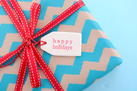 above 25: Festive Christmas red and aqua blue gift with  Happy Holidays gift tag on pale blue wood table.