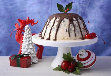 comida de navidad: El verano de Navidad Ice Cream Plum Pudding en la torta blanca de pie con renos y adornos en un entorno azul y blanco moderno.