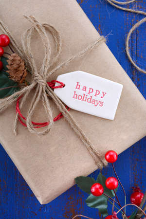 gift wrapping: Gift wrapping presents in natural rustic theme brown kraft paper with string and ornaments on a dark blue rustic wooden table.