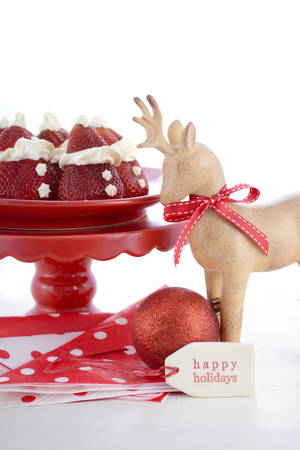 wooden reindeer: Strawberry Santas on red and white polka plate on red cake stand with wooden reindeer ornament on a white wood table for fun, cute Christmas festive party food.