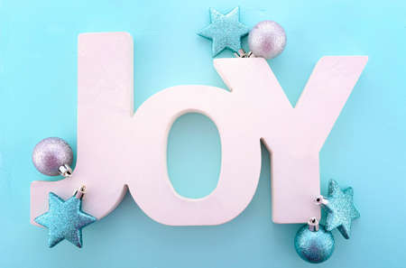 above 25: Festive Christmas greeting, with the word, Joy, spelled in wooden letters with ornaments on a pale blue background.