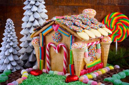 casita de dulces: Festivo de la Navidad Casa de pan de jengibre decorado con bastones de caramelo, conos de malvavisco, chocolates y dulces en un entorno rústico de madera oscura.