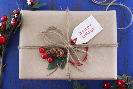 red paper: Gift wrapping presents in natural rustic theme brown kraft paper with string and ornaments on a dark blue rustic wooden table.