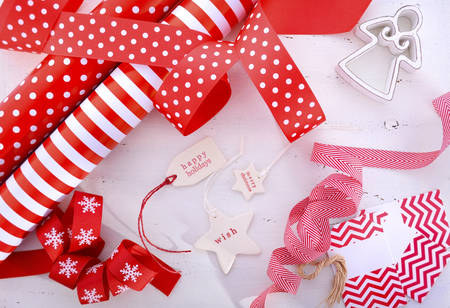 above 25: Red and white theme Christmas gift wrapping with rolls of stripe and polka dot gift paper, festive ribbons and gift tags on white wood table.