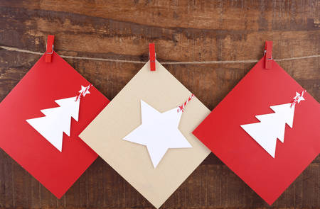 clothespin: Handmade Christmas greeting card using cutout shapes on natural kraft paper hanging from pegs on string line. Stock Photo